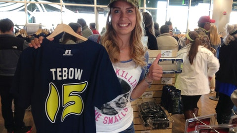 Noelle Colligan shows off the Tim Tebow jersey she bought just before Tebow's professional baseball debut with the Class A Columbia Fireflies in Columbia, S.C., Thursday, April 6, 2017. Colligan said she has been a Tebow fan since he won the Heisman Trophy playing football for Florida in 2007.  (AP Photo/Jeffrey Collins)