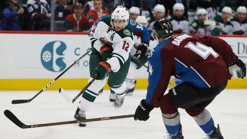 Minnesota Wild center Eric Staal, center, takes a shot as he skates between Colorado Avalanche defensemen Tyson Barrie, front, and Anton Lindholm, of Sweden, in the second period of an NHL hockey game Thursday, April 6, 2017, in Denver. (AP Photo/David Zalubowski)
