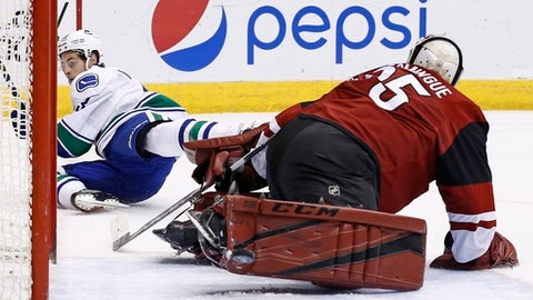 Arizona Coyotes' Louis Domingue, right, makes a save on a shot by Vancouver Canucks' Griffen Molino, left, during the first period of an NHL hockey game Thursday, April 6, 2017, in Glendale, Ariz. (AP Photo/Ross D. Franklin)