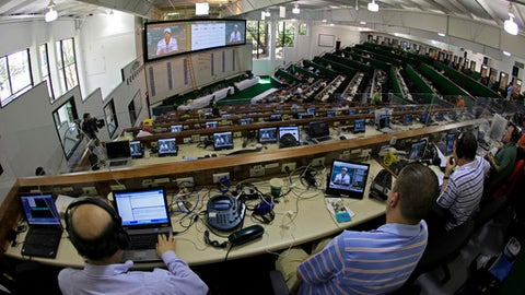 FILE - In this April 5, 2010, file photo, members of the media watch Tiger Woods' news conference from the media center at the Masters golf tournament in Augusta, Ga. Covering the Masters is not hard work, not after Augusta National unveiled a new press center that could be mistaken for a Ritz-Carlton. But somebody has to do it. There are plush chairs and two screens at every wood-paneled desk and just steps away, a lounge, full-service restaurant, takeout food counter, snazzy stone porch, locker room with showers and interview room the United Nations would envy. (AP Photo/Charlie Riedel, FIle)