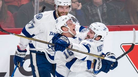 Tampa Bay Lightning's Nikita Kucherov, right, celebrates his goal with teammates Ondrej Palat and Victor Hedman, back, during first-period NHL hockey action against the Montreal Canadiens in Montreal, Friday, April 7, 2017. (Paul Chiasson/The Canadian Press via AP)