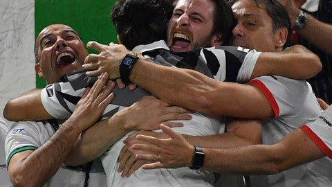 Italian team members embrace Simone Bolelli after he and Andreas Seppi beat Belgium's Ruben Bemelmans and Joris De Loore, during their Davis Cup World Group Quarterfinal match, in the Spiroudome de Charleroi stadium, in Charleroi, Belgium, Saturday, April 8, 2017. (AP Photo/Geert Vanden Wijngaert)