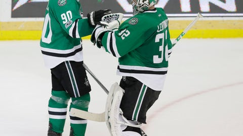 Dallas Stars goalie Kari Lehtonen (32) is congratulated by teammate Jason Spezza (90) after an NHL hockey game against the Colorado Avalanche in Dallas, Saturday, April 8, 2017. The Stars won 4-2 in an overtime shootout. (AP Photo/LM Otero)