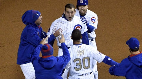 Chicago Cubs Anthony Rizzo, center, celebrates with his teammates after hitting a game winning RBI single against the Los Angeles Dodgers during the ninth inning of a baseball game on home opening day, Monday, April 10, 2017, in Chicago. The Cubs won 3-2. (AP Photo/David Banks)