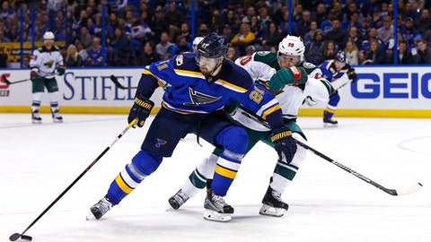 FILE - In this Nov. 26, 2016, file photo, St. Louis Blues' Patrik Berglund, left, of Sweden, reaches for the puck as he is pressured by Minnesota Wild's Ryan Suter during an NHL hockey game, in St. Louis. Here comes Minnesota's first-round opponent, none other than the surging St. Louis team coached by former Wild bench boss Mike Yeo. The Blues were ousted in the Western Conference quarterfinals by the Wild two years ago. (AP Photo/Billy Hurst, File)