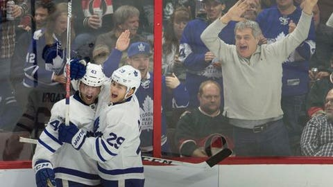 FILE - In this Jan. 14, 2017, file photo, fans react as Toronto Maple Leafs center Nazem Kadri, left, celebrates his second goal with teammate William Nylander during the third period of an NHL hockey game against the Ottawa Senators, in Ottawa, Ontario. Canada ever back in the Stanley Cup playoffs. The buzz is back north of the border with five of the nation's seven teams making the playoffs a year after the hockey-mad country was shut out. (Adrian Wyld/The Canadian Press via AP, File)