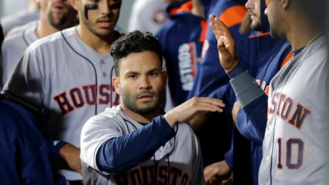 Houston Astros' Jose Altuve, center, is greeted in the dugout after he scored against the Seattle Mariners during the ninth inning of a baseball game Tuesday, April 11, 2017, in Seattle. (AP Photo/Ted S. Warren)