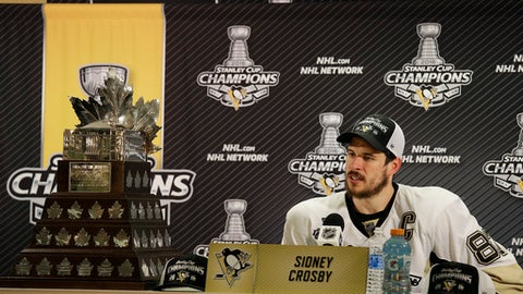FILE - In this June 12, 2016, file photo, Pittsburgh Penguins center Sidney Crosby speaks next to the Conn Smythe Trophy during a news conference after Game 6 of the NHL hockey Stanley Cup Finals between the San Jose Sharks and the Penguins, in San Jose, Calif. There are 16 teams alive for the Stanley Cup when the 2017 playoffs begin. Only one, however, enters as the defending champion. The Pittsburgh Penguins will try to become the first team since the Detroit Red Wings in 1997 and 1998 to win consecutive championships. (AP Photo/Eric Risberg, File)