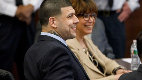 Former New England Patriots tight end Aaron Hernandez smiles as he sits at the defense table during jury deliberations in his double murder trial of at Suffolk Superior Court in Boston, Mass., Wednesday, April 12, 2017. Hernandez is charged in the July 2012 killings of Daniel de Abreu and Safiro Furtado who he encountered in a Boston nightclub. The former NFL football player already is serving a life sentence in the 2013 killing of semi-professional football player Odin Lloyd. (Keith Bedford/The Boston Globe via AP, Pool)