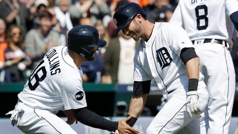 Detroit Tigers' Andrew Romine is greeted at home by Tyler Collins after a grand slam during the fourth inning of a baseball game against the Minnesota Twins, Wednesday, April 12, 2017, in Detroit. (AP Photo/Carlos Osorio)