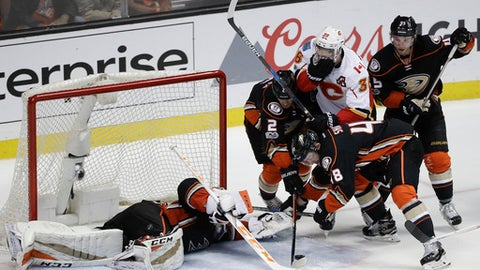 Calgary Flames' Troy Brouwer (36) is defended by Anaheim Ducks' Kevin Bieksa (2) and Logan Shaw (48) as Ducks goalie John Gibson falls to the ice trying to stop a shot during the third period in Game 1 of a first-round NHL hockey Stanley Cup playoff series Thursday, April 13, 2017, in Anaheim, Calif. The Ducks won 3-2. (AP Photo/Jae C. Hong)