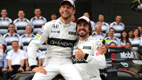 FILE - This is a Friday Oct 7, 2016  file photo of McLaren driver's Jenson Button, left, of Britain and Fernando Alonso of Spain as they pose for a photo with their team in front of their pit lane garage ahead of the first practice session for the Japanese Formula One Grand Prix at the Suzuka International Circuit in Suzuka, Japan. Although the 37-year-old Button retired at the end of last season, he is taking Alonso's seat for the Monaco Grand Prix for a single race because McLaren has allowed Alonso to make his IndyCar debut at the Indianapolis 500 on May 28 2017.  (AP Photo/Eugene Hoshiko, File)