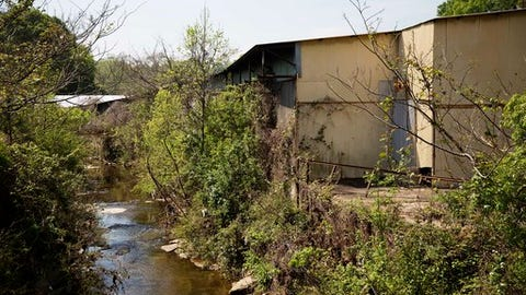 A section of Proctor Creek flows through an old welding plant in Atlanta, Thursday, April 13, 2017. Growing up, Mark Teixeira loved playing at a park near his home. Now, he's trying to bring those same opportunities to an impoverished area in his second home. Hopefully the retired baseball star will lead others to become eco-athletes, lending their considerable influence and financial power to one of the world's most pressing issues: preserving the environment. (AP Photo/David Goldman)