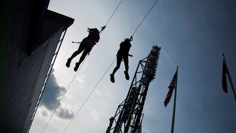 Participants ride a zip line at SunTrust Park before for an opening day baseball game between the Atlanta Braves and the San Diego Padres in Atlanta, Friday, April 14, 2017. The Braves are playing their first regular-season game in SunTrust Park, the new suburban stadium that replaced Turner Field. (AP Photo/David Goldman)