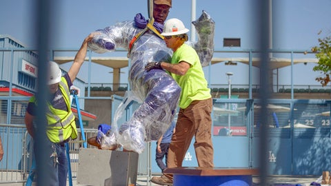 In this April 10, 2017, photo provided by the Los Angeles Dodgers, workers install a bronze statue of Dodgers legend Jackie Robinson outside Dodger Stadium in Los Angeles. Robinson was the first black man to play in the major leagues, ending six decades of racial segregation, and a first-ballot Hall of Famer. He is the first to be honored with a statue at Dodger Stadium. It will be unveiled Saturday, April 15, 2017, on the 70th anniversary of his debut with the Brooklyn Dodgers. (Rowan Kavner/Los Angeles Dodgers via AP)