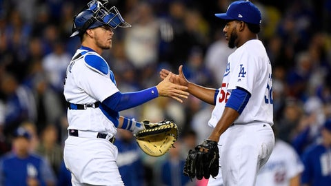 Los Angeles Dodgers catcher Yasmani Grandal, left, congratulates relief pitcher Pedro Baez after the Dodgers defeated the Arizona Diamondbacks 7-1 in a baseball game, Friday, April 14, 2017, in Los Angeles. (AP Photo/Mark J. Terrill)