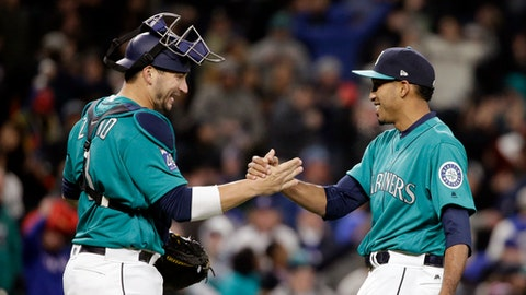 Seattle Mariners catcher Mike Zunino, left, and closing pitcher Edwin Diaz share congratulations after the final out of a baseball game against the Texas Rangers on Friday, April 14, 2017, in Seattle. The Mariners won 2-1. (AP Photo/Elaine Thompson)