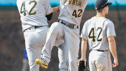 Pittsburgh Pirates' Phil Gosselin, left, celebrates with Starling Marte, center, their win over the Chicago Cubs, Saturday, April 15, 2017, in Chicago. (AP Photo/Kamil Krzaczynski)
