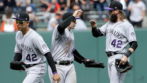 Colorado Rockies outfielders Carlos Gonzalez, from left, Stephen Cardullo and Charlie Blackmon celebrate after a baseball game against the San Francisco Giants in San Francisco, Saturday, April 15, 2017. The Rockies won 5-0. Both teams wore wearing number 42 in tribute of Jackie Robinson. (AP Photo/Jeff Chiu)