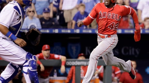 Los Angeles Angels' Cameron Maybin runs home past Kansas City Royals catcher Salvador Perez to score on a single by Ben Revere during the seventh inning of a baseball game, Saturday, April 15, 2017, in Kansas City, Mo. (AP Photo/Charlie Riedel)
