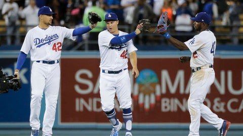 Los Angeles Dodgers' Yasiel Puig, Joc Pederson and Trayce Thompson, from right, celebrate the team's 8-4 win over the Arizona Diamondbacks in a baseball game, Saturday, April 15, 2017, in Los Angeles. (AP Photo/Jae C. Hong)