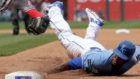 Kansas City Royals' Lorenzo Cain beats the tag by Los Angeles Angels first baseman C.J. Cron as he slides back to first on a pick off attempt during the third inning of a baseball game Sunday, April 16, 2017, in Kansas City, Mo. (AP Photo/Charlie Riedel)