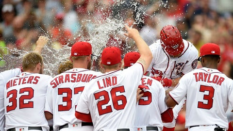 Washington Nationals' Bryce Harper, second from right, is mobbed by teammates at home after a baseball game against the Philadelphia Phillies, Sunday, April 16, 2017, in Washington. Harper hit a three-run walkoff homerun. The Nationals won 6-4. (AP Photo/Nick Wass)