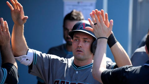 Arizona Diamondbacks' A.J. Pollock is congratulated by teammates after scoring on a single by Paul Goldschmidt during the seventh inning of a baseball game, Sunday, April 16, 2017, in Los Angeles. (AP Photo/Mark J. Terrill)