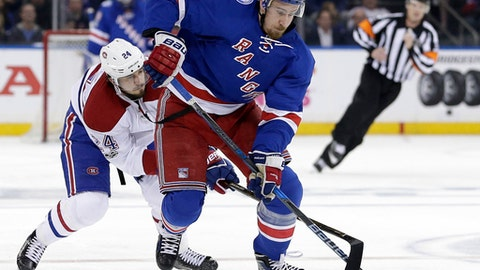 New York Rangers' Kevin Hayes, right, and Montreal Canadiens' Phillip Danault reach for the puck during the second period in Game 3 of an NHL hockey first-round playoff series, Sunday, April 16, 2017, in New York. (AP Photo/Seth Wenig)