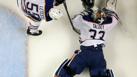 Edmonton Oilers goalie Cam Talbot (33) lays out to stop a shot next to San Jose Sharks center Tomas Hertl, top, and Oilers' Mark Letestu (55) during the second period in Game 3 of a first-round NHL hockey playoff series Sunday, April 16, 2017, in San Jose, Calif. (AP Photo/Marcio Jose Sanchez)