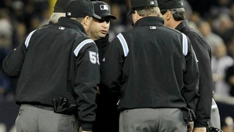 FILE - This Oct. 19, 2010, file photo shows umpires huddling after an apparent home run by New York Yankees' Lance Berkman in the second inning of Game 4 of baseball's American League Championship Series against the Texas Rangers in New York. Major League Baseball umpires could start explaining replay decisions to the players and fans _ the way NFL referees do _ later this season if the sides can reach agreement. Under one possible scenario, the crew chief could wear a microphone beginning at the All-Star Game. (AP Photo/Kathy Willens, File)