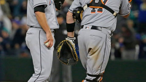 Miami Marlins closing pitcher Kyle Barraclough, left, stands on the mound with catcher A.J. Ellis after Barraclough gave up a double to Seattle Mariners' Mitch Haniger that broke up a combined no-hitter in the ninth inning of a baseball game, Tuesday, April 18, 2017, in Seattle. The Marlins won 5-0. (AP Photo/Ted S. Warren)