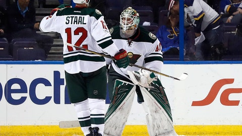 Minnesota Wild goalie Devan Dubnyk, right, and Eric Staal celebrate following the team's 2-0 victory over the St. Louis Blues in Game 4 of an NHL hockey first-round playoff series Wednesday, April 19, 2017, in St. Louis. (AP Photo/Jeff Roberson)