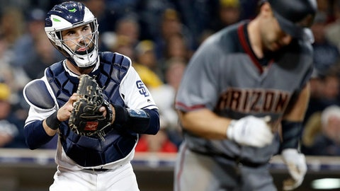 San Diego Padres catcher Austin Hedges, left, prepares to throw the ball to first to get Arizona Diamondbacks Paul Goldschmidt, after Goldschmidt struck out during the seventh inning of a baseball game in San Diego, Thursday, April 20, 2017. (AP Photo/Alex Gallardo)