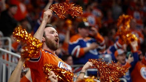 An Edmonton Oilers fan cheers the team's tying goal against the San Jose Sharks during the third period of Game 5 of a first-round NHL hockey Stanley Cup playoff series, Thursday, April 20, 2017, in Edmonton, Alberta. (Jeff McIntosh/The Canadian Press via AP)