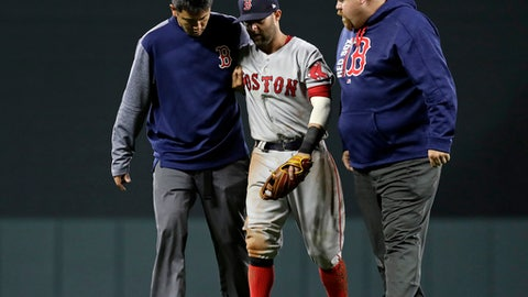 Boston Red Sox second baseman Dustin Pedroia, center, is assisted off the field after being injured during the eighth inning of the team's baseball game against the Baltimore Orioles in Baltimore, Friday, April 21, 2017. (AP Photo/Patrick Semansky)