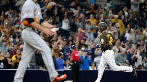 Miami Marlins pitcher David Phelps waits as San Diego Padres' Austin Hedges, right, rounds third base after hitting a three-run home run during the seventh inning of a baseball game in San Diego, Friday, April 21, 2017. (AP Photo/Christine Cotter)