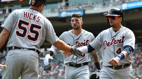 Detroit Tigers designated hitter Victor Martinez, right, gets a handshake from teammate John Hicks after he and Nicholas Castellanos, rear, scored on Jim Adduci's double off Minnesota Twins starting pitcher Kyle Gibson in the third inning of a baseball game, Sunday, April 23, 2017, at Target Field in Minneapolis. (AP Photo/John Autey)
