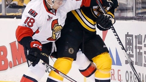 Boston Bruins' Dominic Moore (28) and Ottawa Senators' Ryan Dzingel (18) battle for the puck during the first period in Game 6 of a first-round NHL hockey Stanley Cup playoff series Sunday, April 23, 2017, in Boston. (AP Photo/Michael Dwyer)