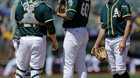 Oakland Athletics' Andrew Triggs (60) speaks with pitching coach Curt Young, left, in the third inning of a baseball game against the Seattle Mariners Sunday, April 23, 2017, in Oakland, Calif. (AP Photo/Ben Margot)