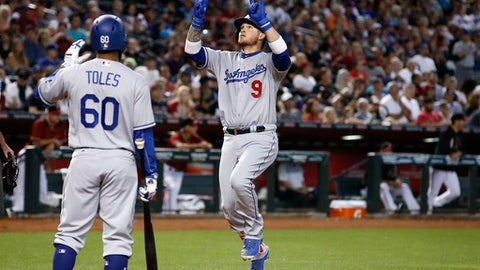 Los Angeles Dodgers' Yasmani Grandal (9) celebrates his two-run home run against the Arizona Diamondbacks as Dodgers' Andrew Toles (60) waits to give a high-five during the fifth inning of a baseball game Sunday, April 23, 2017, in Phoenix. (AP Photo/Ross D. Franklin)