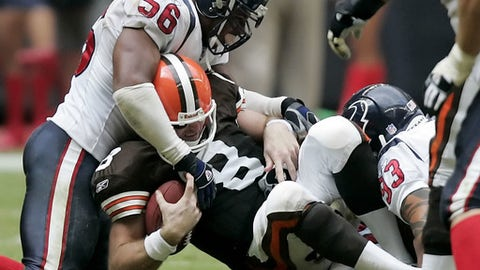 FILE - In this Sunday, Oct. 30, 2005, file photo, Cleveland Browns quarterback Trent Dilfer (8) is sacked by Houston Texans' Morlon Greenwood (56), Gary Walker (96) and Jason Babin (93) during the fourth quarter in Houston. For nearly two decades, the Browns, once a standard of NFL excellence and now a league punching bag, have been running in circles as they try to find a quarterback to lead them from the darkness to relevance and respectability. From Tim Couch to Dilfer, from Derek Anderson to Cody Kessler, and let's not forget that year of fun with Johnny Manziel, QBs have cycled through Cleveland like tourists with none sticking around for long. (AP Photo/David J. Phillip, File)