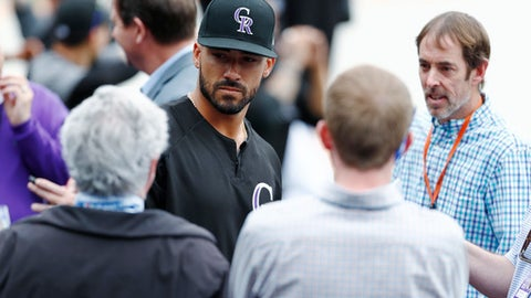Colorado Rockies first baseman Ian Desmond, back center, talks to reporters after taking batting practice for the first time since his hand was broken by a pitch during spring training as the Rockies prepare to face the Washington Nationals in a baseball game Monday, April 24, 2017, in Denver. (AP Photo/David Zalubowski)