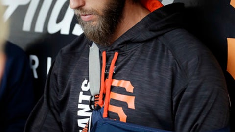 San Francisco Giants pitcher Madison Bumgarner sits in the dugout with his arm in a sling from a recent injury before a baseball game against the Los Angeles Dodgers, Monday, April 24, 2017, in San Francisco . (AP Photo/Marcio Jose Sanchez)