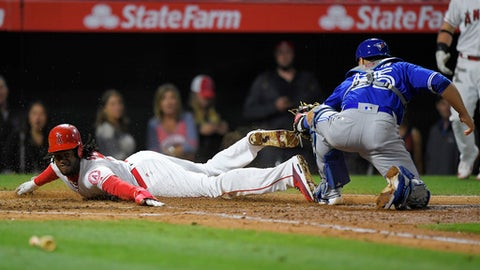Los Angeles Angels' Cameron Maybin, left, scores on fielder's choice hit by David Hernandez as Toronto Blue Jays catcher Russell Martin makes a late tag during the fifth inning of a baseball game, Monday, April 24, 2017, in Anaheim, Calif. (AP Photo/Mark J. Terrill)