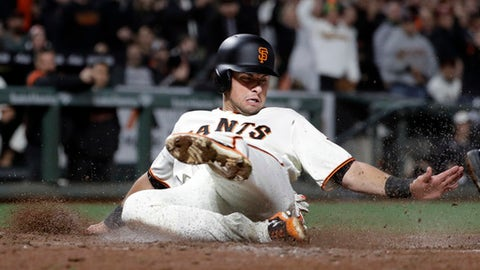 San Francisco Giants' Joe Panik slides into home plate to score on a single from Hunter Pence during the seventh inning of a baseball game against the Los Angeles Dodgers, Monday, April 24, 2017, in San Francisco. (AP Photo/Marcio Jose Sanchez)
