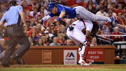 Toronto Blue Jays' Chris Coghlan scores, leaping over St. Louis Cardinals catcher Yadier Molina during the seventh inning of a baseball game Tuesday, April 25, 2017, in St. Louis. The Blue Jays won 6-5 in 11 innings. (Christian Gooden/St. Louis Post-Dispatch via AP)