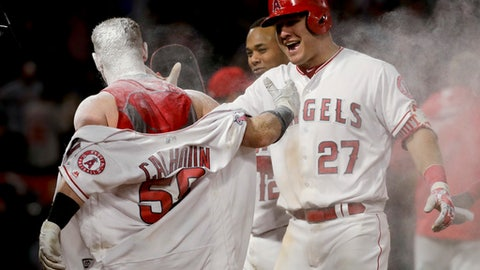 Los Angeles Angels' Kole Calhoun, left, celebrates his game-winning single with Mike Trout during the 11th inning of a baseball game in Anaheim, Calif., Tuesday, April 25, 2017. The Angels won 2-1. (AP Photo/Chris Carlson)