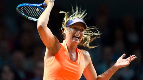 Maria Sharapova of Russia plays a shot to Italy's Roberta Vinci during the Grand Prix tennis tournament in Stuttgart, Germany, Wednesday, April 26, 2017. Sharapova was given a lukewarm welcome by 4,500 spectators upon her return to professional tennis on Wednesday after a 15-month doping ban. (Daniel Maurer/dpa via AP)
