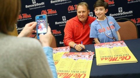Mississippi football coach Hugh Freeze poses with Cooper Hughes, 13, as Cooper's mother, Terri, snaps a photo Wednesday evening, April 26, 2017, during the Rebel Roadshow in Tupelo, Miss. (Lauren Wood/Northeast Mississippi Daily Journal via AP)